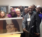 Staff and delegation posing with photo of Maureen as a young nun