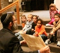 Rabbie Druin with a Torah scroll befor a group of children